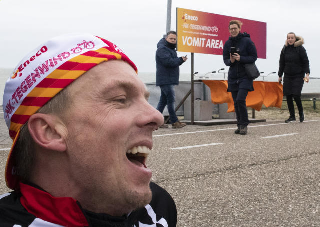 Wouter de Jonge catches his breath in the vomit area after battling gale force winds during the Dutch Headwind Cycling Championships on the storm barrier Oosterscheldekering near Neeltje Jans, south-western Netherlands, Sunday, Feb. 9, 2020. (AP Photo/Peter Dejong)