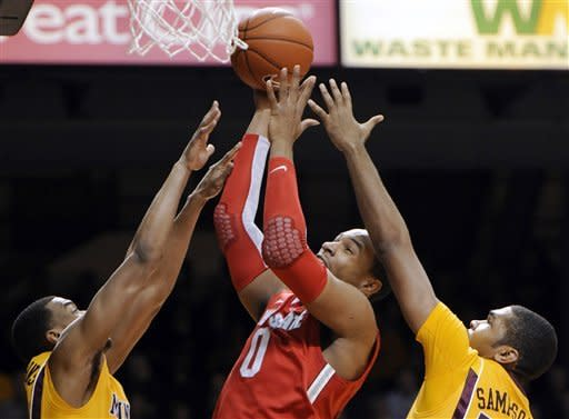 Ohio State's Jared Sullinger (0) shoots as Minnesota's Andre Hollins, left, and Ralph Sampson III defend in the first half during an NCAA college basketball game in Minneapolis on Tuesday, Feb. 14, 2012. Sampson was called for a foul on the play. (AP Photo/Hannah Foslien)