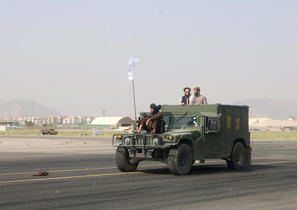 Taliban forces use an armoured vehicle to patrol along the runway at Kabul airport (REUTERS)