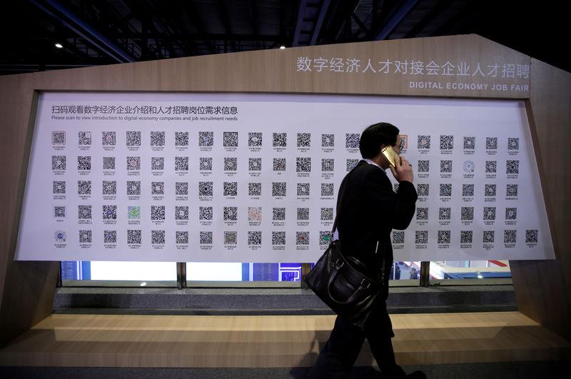 A man walks past a poster showing the QR codes for job-seeking information during an internet expo at the fifth WIC in Wuzhen