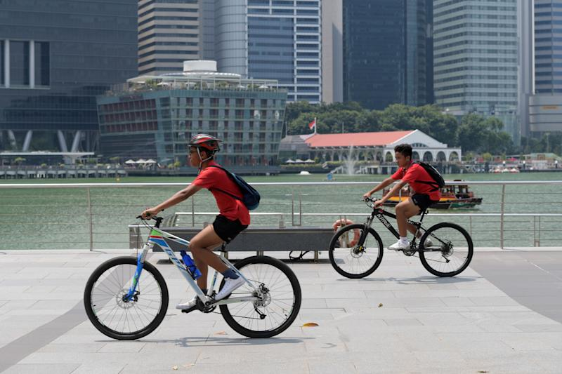 Boys ride their bicycles along the Marina Bay promenade in Singapore on October 10, 2019. (Photo by Roslan RAHMAN / AFP) (Photo by ROSLAN RAHMAN/AFP via Getty Images)