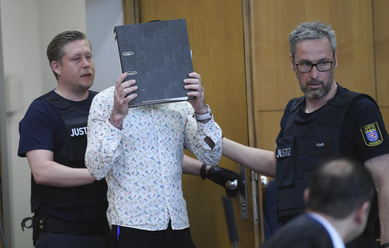 At the opening of the trial, the defendant covers his face with a folder as he arrives in the courtroom at the Higher Regional Court (OLG) in Frankfurt, Germany, Friday, April 24, 2020. The 37-year-old Iraqi defendant on suspicion of the murder of a five-year-old girl in Syria . The Federal Prosecutor's Office also charges him with genocide, membership of a terrorist organisation and human trafficking. (Arne Dedert/Pool via AP)