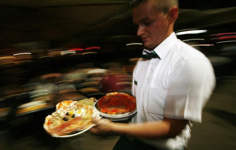 A waiter carries pizzas at the Ai Marmi restaurant in the Rome neighborhood of Trastevere