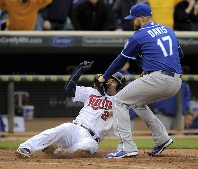 Kansas City Royals pitcher Wade Davis (17) puts a late tag on the Minnesota Twins' Brian Dozier, who scored with the go-ahead run during the ninth inning of a baseball game in Minneapolis, Sunday, April 13, 2014. Minnesota won 4-3. (AP Photo/Tom Olmscheid)