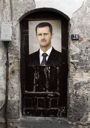 A portrait of Syria's President Bashar al-Assad is affixed on a door in old Damascus, September 8, 2013. REUTERS/Khaled al-Hariri