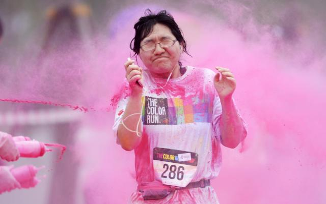 A woman reacts as she is sprayed with colour powder during a five-kilometre colour run event in Beijing June 21, 2014. REUTERS/China Daily (CHINA - Tags: SPORT ATHLETICS SOCIETY TPX IMAGES OF THE DAY) CHINA OUT. NO COMMERCIAL OR EDITORIAL SALES IN CHINA