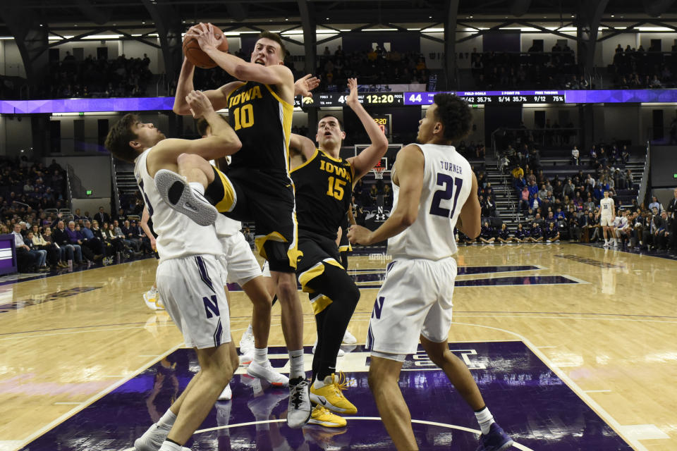 Iowa guard Joe Wieskamp (10) grabs a rebound in front of Northwestern center Ryan Young, left, during the second half of an NCAA college basketball game Tuesday, Jan. 14, 2020, in Evanston, Ill. (AP Photo/David Banks)