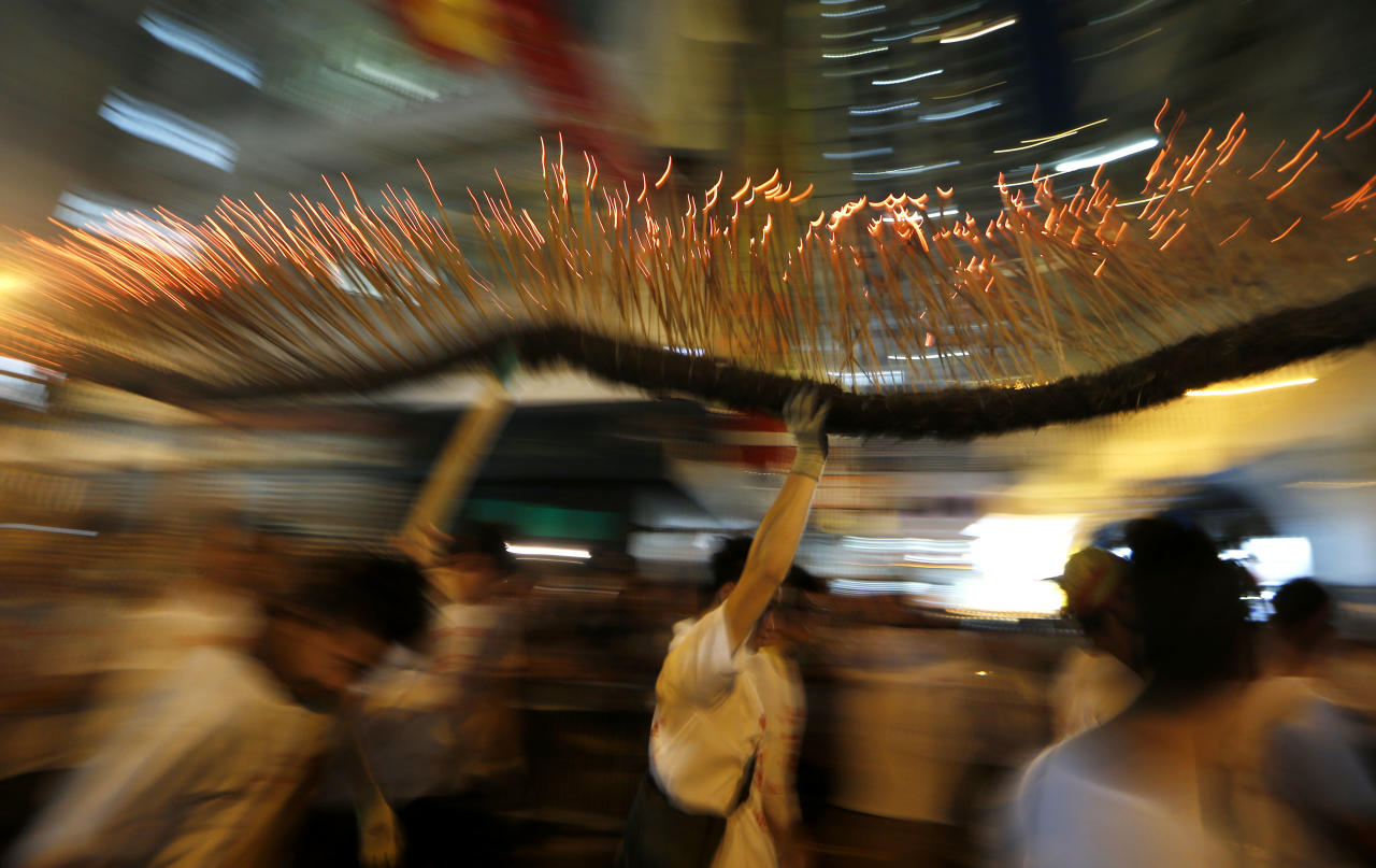 A dragon made of incense sticks is paraded during the Fire Dragon Dance performance through a Hong Kong street Saturday, Sept. 29, 2012. The Fire Dragon Dance is a spectacular celebration of local culture during the mid-autumn festival. (AP Photo/Kin Cheung)