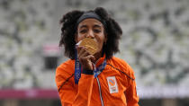 Sifan Hassan, of Netherlands, kisses her gold medal for women's 5,000-meters final at the 2020 Summer Olympics, Tuesday, Aug. 3, 2021, in Tokyo. (AP Photo/Francisco Seco)