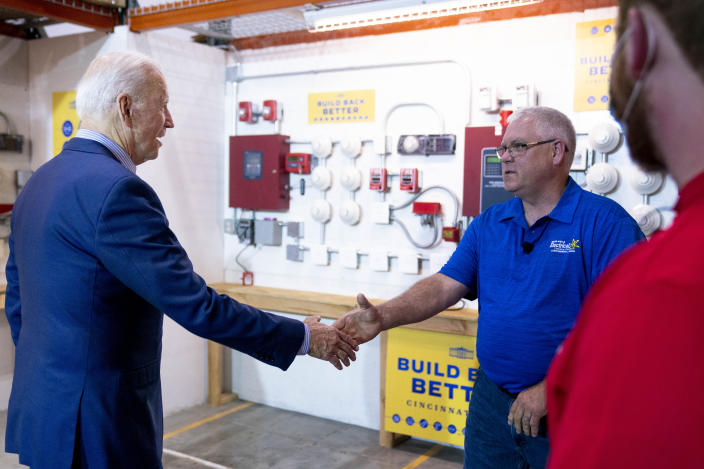 President Joe Biden greets electrician instructor Jerry Mahoney, second from right, and apprentice Stephen Randolph, right, as he arrives to speak with them at the IBEW / NECA Electrical Training Center in Cincinnati, Wednesday, July 21, 2021. (AP Photo/Andrew Harnik)