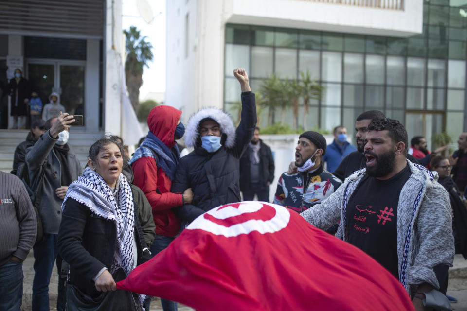 A small group of people take part in a protest on the tenth anniversary of the uprising that toppled longtime autocrat Ben Ali , during to a national lockdown after a surge in COVID-19 cases, in Tunis, Thursday, Jan. 14, 2021. Tunisia is commemorating the 10th anniversary since the flight into exile of its iron-fisted leader, Zine El Abidine Ben Ali, pushed from power in a popular revolt that foreshadowed the so-called Arab Spring. But there will be no festive celebrations Thursday marking the revolution in this North African nation, ordered into lockdown to contain the coronavirus. (AP Photo/Mosa'ab Elshamy)