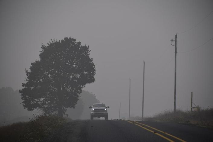 A truck drives on a road shrouded in smoke and fog in Sublimity, Oregon near the east edge of the Beachie Creek Fire, September 14, 2020.