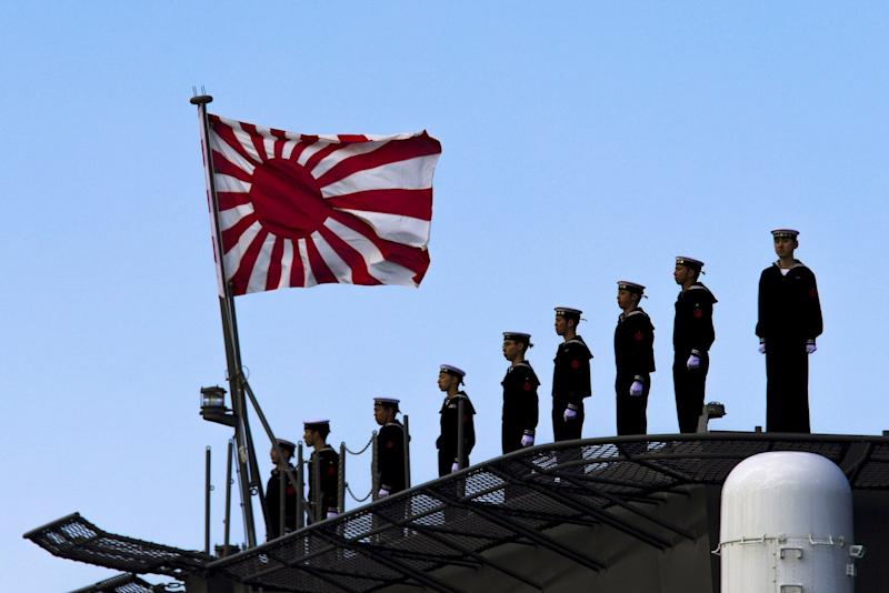 Sailors stand on the deck of the Izumo warship as it departs from the harbour of the Japan United Marine shipyard in Yokohama, south of Tokyo March 25, 2015.