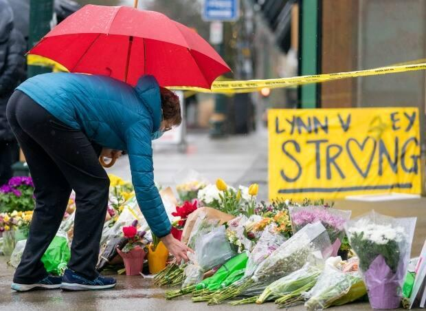 A makeshift memorial outside the Lynn Valley public library in North Vancouver pictured on March 28, the day after a woman was killed and six people injured in a series of stabbing attacks there. (Jonathan Hayward/Canadian Press - image credit)