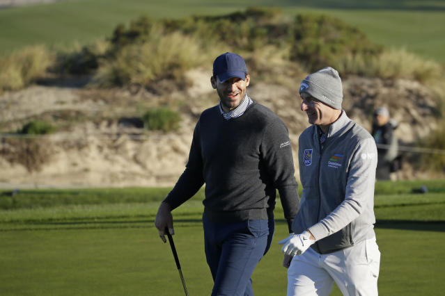Tony Romo, left, talks with Jim Furyk while walking up to the second green of the Spyglass Hill Golf Course during the first round of the AT&T Pebble Beach National Pro-Am golf tournament Thursday, Feb. 6, 2020, in Pebble Beach, Calif. (AP Photo/Eric Risberg)