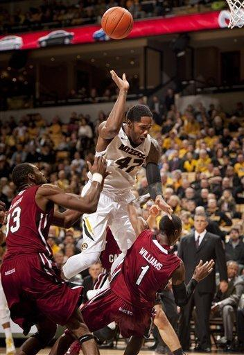 Missouri's Alex Oriakhi, top, is fouls South Carolina's Brenton Williams, right, as he shoots while R.J. Slawson, left, looks on during the first half of an NCAA college basketball game Tuesday, Jan. 22, 2013, in Columbia, Mo. (AP Photo/L.G. Patterson)
