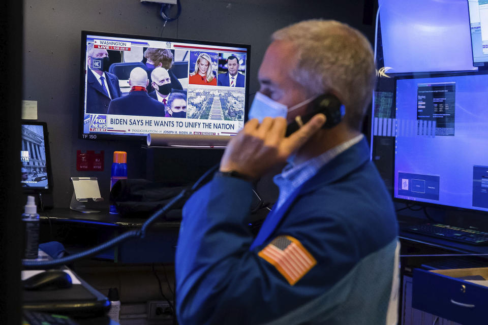 In this photo provided by the New York Stock Exchange, the presidential inaugural plays on a screen as trader Timothy Nick works in a booth on the trading floor, Wednesday, Jan. 20, 2021. U.S. stocks are rallying to records Wednesday on encouraging earnings reports and continued optimism that new leadership in Washington will mean more support for the struggling economy. (Colin Ziemer/New York Stock Exchange via AP)