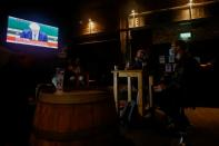 People watch Britain's Prime Minister Boris Johnson making a speech, at a pub, amid the outbreak of the coronavirus disease (COVID-19) in Liverpool