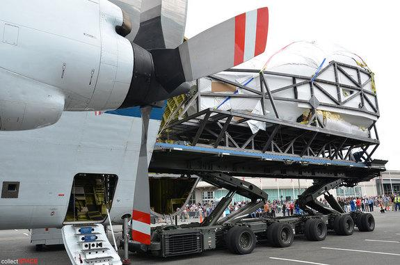 Shrink-wrapped in plastic, the space shuttle crew compartment from NASA Johnson Space Center's Full Fuselage Trainer (FFT) is offload from the space agency's Super Guppy cargo plane onto a military transport at The Museum of Flight in Seattle,