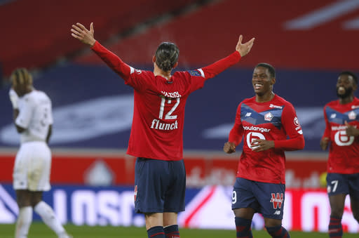 Lille's Yusuf Yazici, center, reacts after scoring during his French League One soccer match between Lille and Lorient in Villeneuve d'Ascq, northern France, Sunday Nov. 22, 2020. (AP Photo/Michel Spingler)