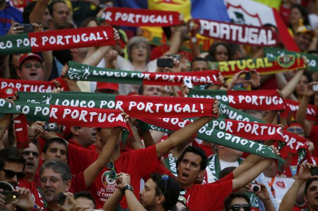 Fans of Portugal hold up scarves as they wait for the start of their 2014 World Cup Group G soccer match against Ghana at the Brasilia national stadium in Brasilia June 26, 2014. REUTERS/Jorge Silva (BRAZIL - Tags: SOCCER SPORT WORLD CUP)
