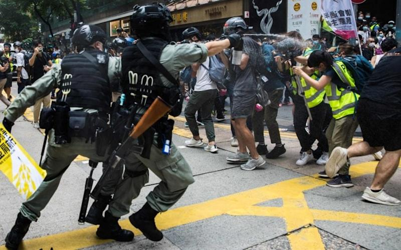 Riot police armed with pepper spray advance on protesters in Hong Kong. CREDIT: GETTY - GETTY