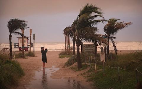 A woman takes a picture as the effects of Hurricane Dorian begin to be felt on Monday in Cocoa Beach, Florida - Credit: Scott Olson/Getty Images North America