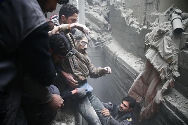 <p>Civil defence help a man from a shelter in the besieged town of Douma in eastern Ghouta in Damascus, Syria, Feb. 22, 2018. (Photo: Bassam Khabieh/Reuters) </p>