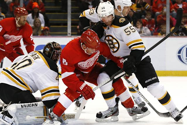 Boston Bruins defenseman Johnny Boychuk (55) defends Detroit Red Wings left wing Justin Abdelkader (8) as he tries to redirect a puck against goalie Tuukka Rask (40), of Finland, in the second period of an NHL hockey game in Detroit, Wednesday, Nov. 27, 2013. (AP Photo/Paul Sancya)