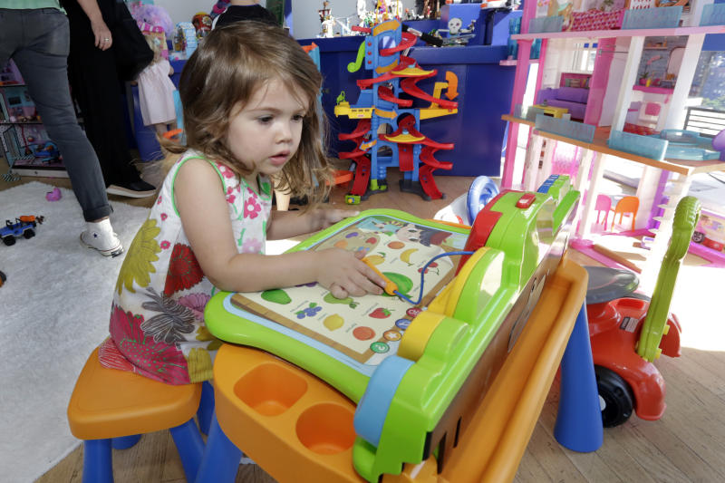 "In this Aug. 30, 2018, photo Seraphina, 3, plays with a V-Tech Explore and Write Activity Set at the Walmart Toy Shop event in New York. Walmart says 30 percent of its holiday toy assortment will be new. It will also offer 40 percent more toys on Walmart.com from a year ago. In November and December, the company's toy area will be rebranded as ""America's Best Toy Shop."" (AP Photo/Richard Drew)"