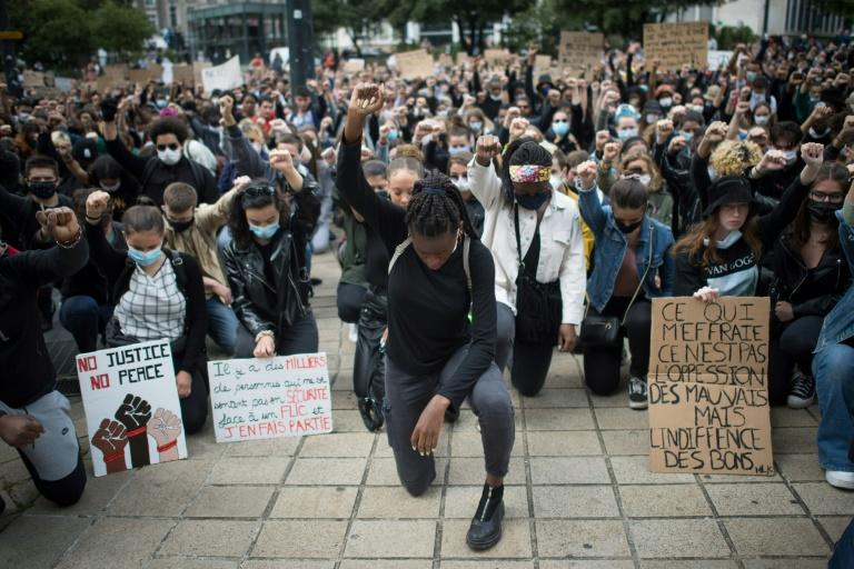Demonstrators dropped to their knees and raised a fist as they turned out to march in the western city of Nantes (AFP Photo/Loic VENANCE)