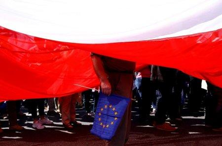 FILE PHOTO: A man holds an EU flag as he stands under a giant Polish flag during an anti-government demonstration organised by main opposition parties in Warsaw, Poland May 7, 2016. To match Special Report POLAND-NATIONALISM/ REUTERS/Kacper Pempel/File Photo