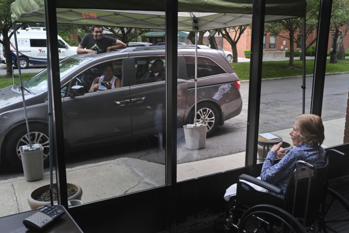 Gloria DeSoto, 92, visits with her family in their car through a window of the Hebrew Home at Riverdale in Bronx, N.Y., on June 11. (Seth Wenig / AP file)