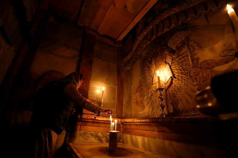 A worshipper inside the renovated Edicule in the Church of the Holy Sepulchre in Jerusalem's old city on March 20, 2017 (AFP Photo/Gali TIBBON)