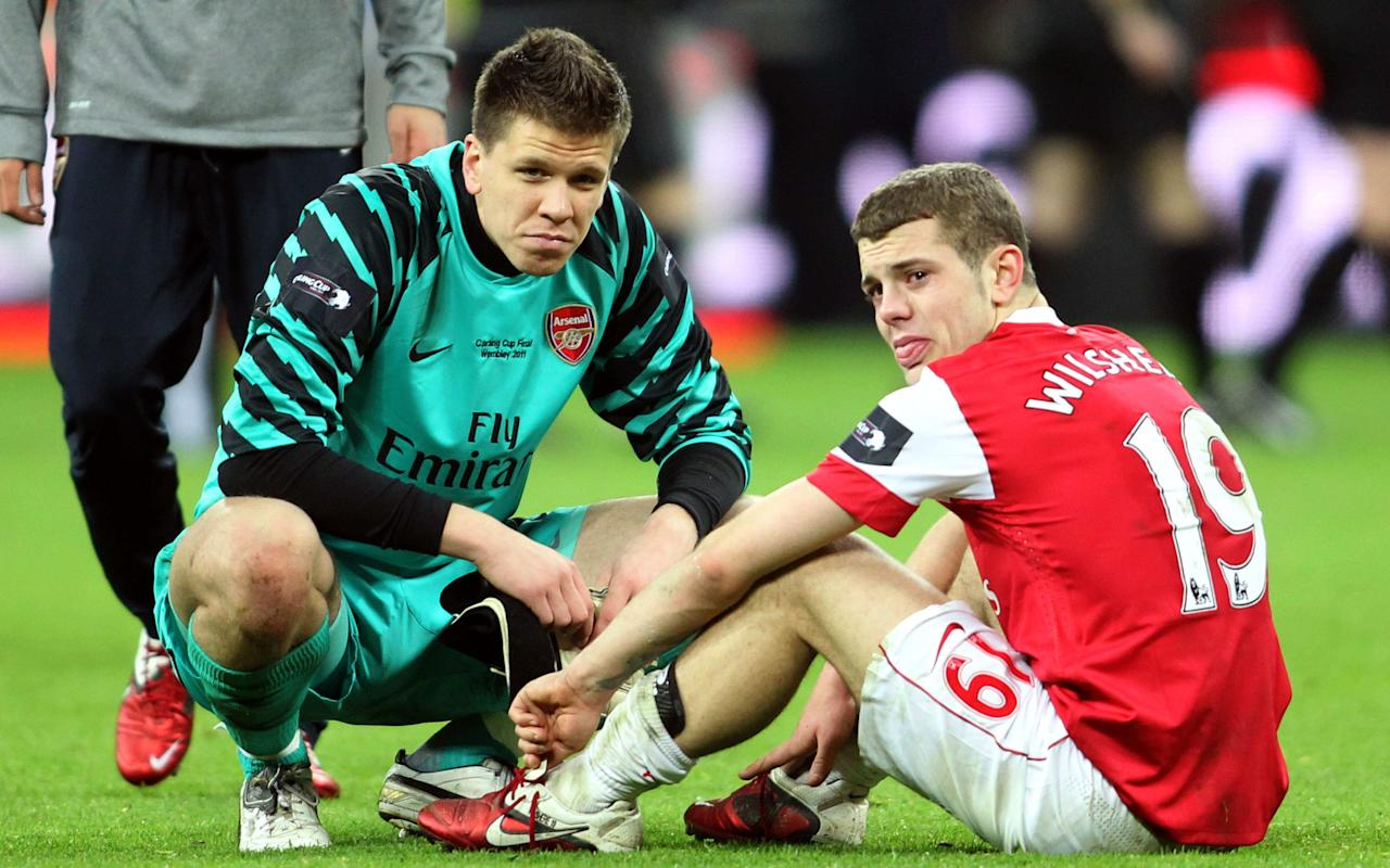 From telling Gary Neville he was ugly while on-loan at Bolton Wanderes to leading the wayon FA Cup-winning open-top bus parades, Jack Wilshere has never been short of a word. Former Arsenal goalkeeper and fellow academy graduate Wocjiech Szczesny was asking for trouble when he posted a light-hearted comment on a Wilshere Instagram post that reminisced on when the pair lived in digs together. Wilshere posted the picture of his teenage self with the comment '#tbtto the digs days and living with the mad man@wojciech.szczesny1can't believe he let me have my hair like this #stillbetterlookingthanhim'. The Juventus goalkeeper responded with 'was that when your were still good at football' in a reference to the months Wilshere has spent on the sidelines through injury. That prompted a swift retort from Wilshere, who reminded Szczesny of his howler against Birmingham City at Wembley 2011 by saying 'no it was when you threw the carling cup away from us'. #tbt to the digs days and living with the mad man @wojciech.szczesny1 can't believe he let me have my hair like this �� #stillbetterlookingthanhim A post shared by Jack Wilshere (@jackwilshere) on Sep 21, 2017 at 11:28am PDT With the score poised at 1-1, Birmingham goalkeeper Ben Foster launched a goal-kick forward that caused confusion between Szczesny and Laurent Koscielny. The Arsenal centre back went to clear as the Pole came rushing out, but his last-minute decision to leave it backfired as the ball rebounded off Szczesny to Obafemi Martins. Arsenal missed a golden opportunity to end their trophy-drought against Alex McLeish's underdogs, and the shock defeat proved a watershed moment in that squad's development. Wilshere, Szczesny, Cesc Fabregas, Abou Diaby and Gael Clichy were among the crop of young player Arsene Wenger wanted to build his team around while money was tight in the years after the Emiratesmove. They never recovered from their Wembley debacle, falling away in the 2011 title race and crashing out of the C