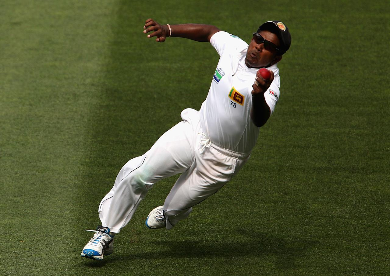 MELBOURNE, AUSTRALIA - DECEMBER 27:  Rangana Herath of Sri Lanka takes a catch to dismiss Michael Hussey of Australia off the bowling of Tillakaratne Dilshan of Sri Lanka during day two of the Second Test match between Australia and Sri Lanka at Melbourne Cricket Ground on December 27, 2012 in Melbourne, Australia.  (Photo by Robert Prezioso/Getty Images)