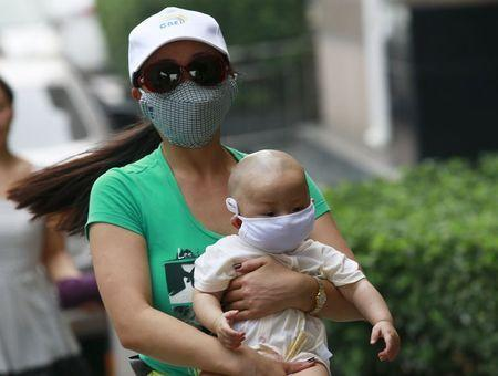 A woman carrying a baby, both wearing masks, make their way down a street in Binhai new district, more than five kilometers (3 miles) away from the site of last week's explosions, in Tianjin, China, August 17, 2015. REUTERS/Kim Kyung-Hoon
