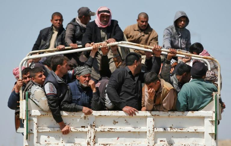 Iraqis who fled their homes in the Old City in western Mosul due to the fighting between government forces and Islamic State group fighters are taken to Hammam al-Alil camp, south of the city