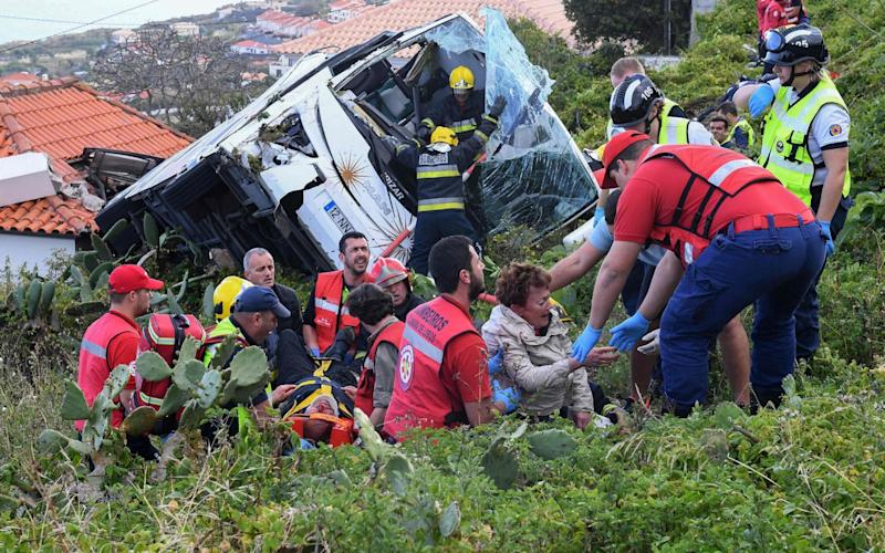 Firemen help victims of a tourist bus that crashed on April 17, 2019 in Caniço, on the Portuguese island of Madeira - AFP