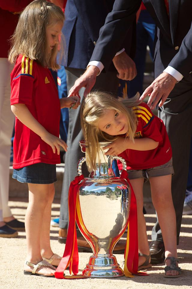 MADRID, SPAIN - JULY 02: Princess Sofia of Spain (R) reaches into the UEFA EURO 2012 trophy while Princess Leonor of Spain watches as King Juan Carlos I of Spain receives players of Spain's victorious national football team at Zarzuela Palace on July 2, 2012 in Madrid, Spain. (Photo by Pool/Getty Images)