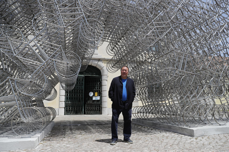 """Dissident Chinese artist Ai Weiwei poses by his sculpture """"Forever Bicycles"""" during a press preview of his new exhibition """"Rapture"""" in Lisbon, Thursday, June 3, 2021. The world-renowned artist is putting on the biggest show of his career, and he is doing it in a place he's fallen in love with: Portugal. (AP Photo/Armando Franca)"""