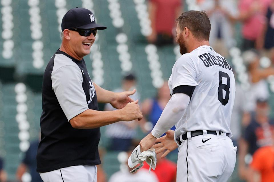 Detroit Tigers left fielder Robbie Grossman (8) is congratulated by manager A.J. Hinch (14)  after he bunts in the winning run in the 10th inning June 27, 2021 against the Houston Astros at Comerica Park.
