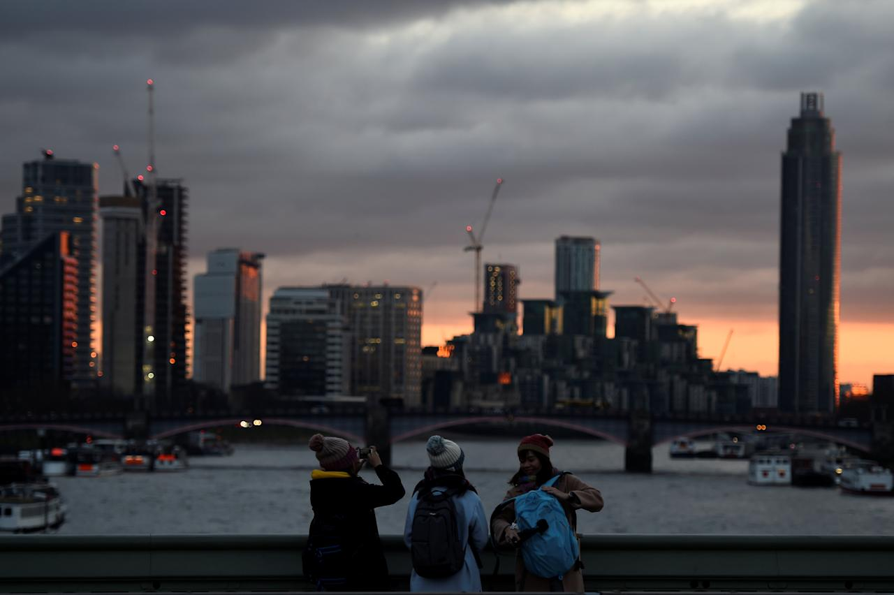 Tourists take pictures on Westminster Bridge during sunset in London, Britain, December 15, 2017. REUTERS/Clodagh Kilcoyne