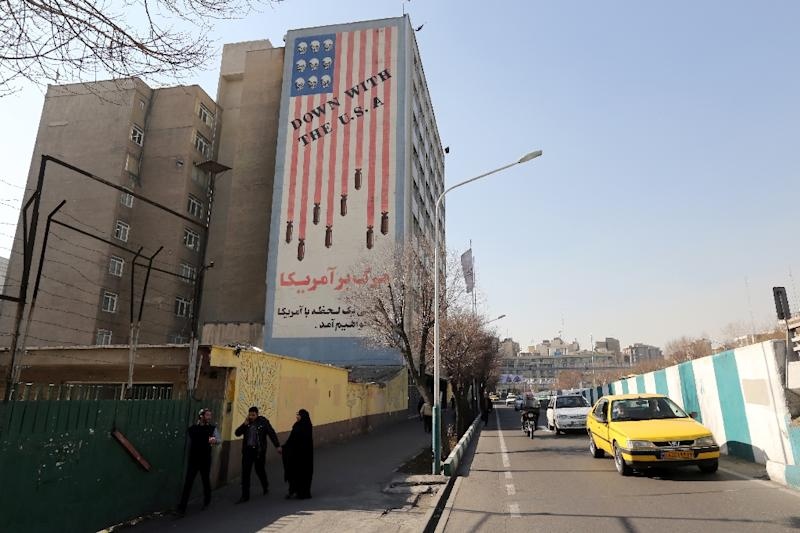 Iranians in Tehran on January 18, 2016 walk past a building painted with anti-US graffiti (AFP Photo/Atta Kenare)