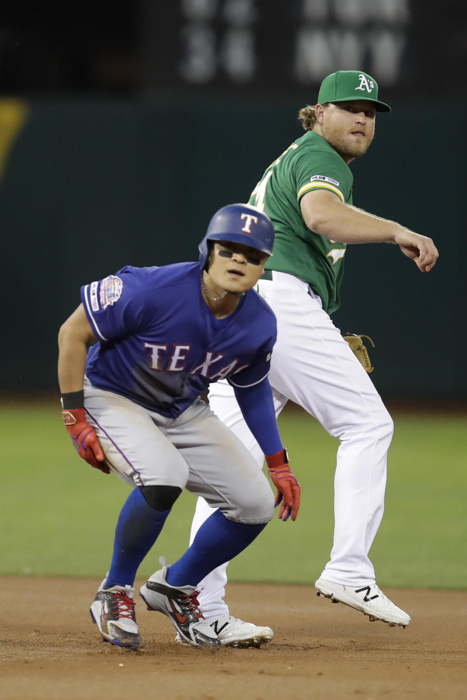 Oakland Athletics Sheldon Neuse, right, and Texas Rangers' Shin-Soo Choo look to first base during a double play in the first inning of a baseball game Friday, Sept. 20, 2019, in Oakland, Calif. Elvis Andrus was out at first base. (AP Photo/Ben Margot)