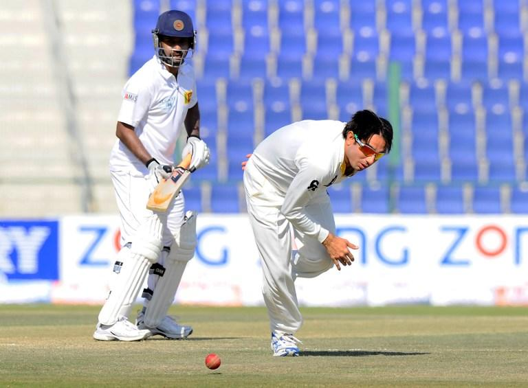 Pakistan bowler Saeed Ajmal (R) fields a ball as Sri Lankan batsmans Prasanna Jayawardene (L) looks on during the final day of the first cricket Test match between Pakistan and Sri Lanka at the Sheikh Zayed Stadium in Abu Dhabi on January 4, 2014. AFP PHOTO/Ishara S. KODIKARA