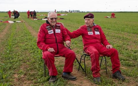 Veteran Harry Read, 95, (left) and Jock Hutton, 94, after completing their tandem parachute jump with the Red Devils - Credit: Jane Barlow/PA