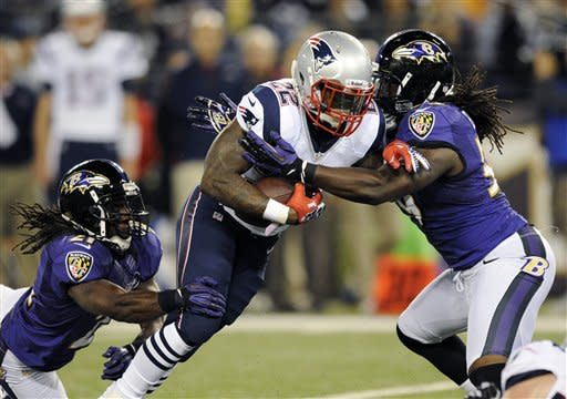 New England Patriots running back Stevan Ridley, center, attempts to rush past Baltimore Ravens cornerback Lardarius Webb, left, and linebacker Dannell Ellerbe in the first half of an NFL football game in Baltimore, Sunday, Sept. 23, 2012. (AP Photo/Nick Wass)