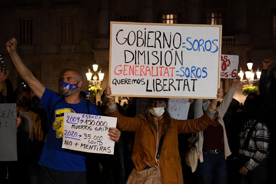 Protesters hold signs calling for freedom and the resignation of the government along with a placard comparing the number of coronavirus deaths with the number of flu deaths during a demonstration against new coronavirus restrictions in Barcelona on October 30, 2020. - One by one, Spain's regions have announced regional border closures in the hope of avoiding a new lockdown like in France. The central government unveiled a state of emergency to give regional authorities the tools to impose curfews and close their borders to anyone moving without just cause. (Photo by Josep LAGO / AFP) (Photo by JOSEP LAGO/AFP via Getty Images)