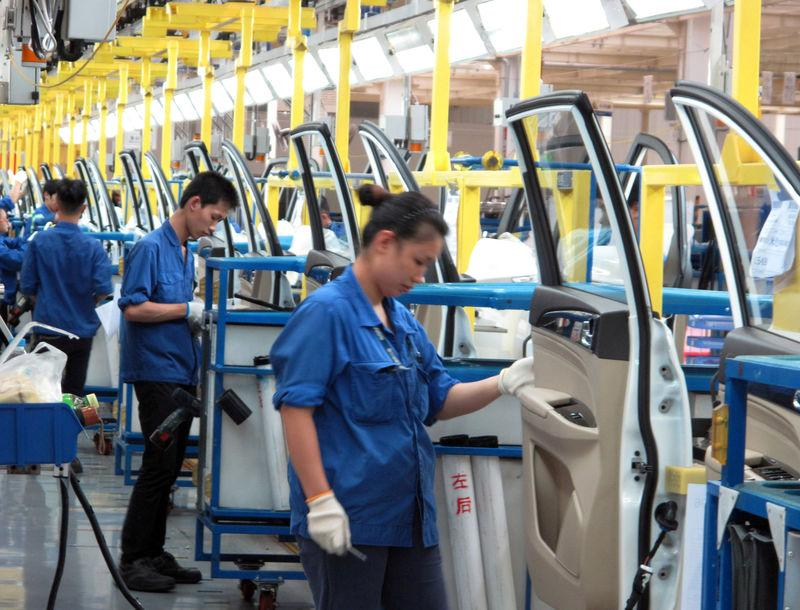 FILE PHOTO: Employees work at a production line inside a factory of Saic GM Wuling, in Liuzhou